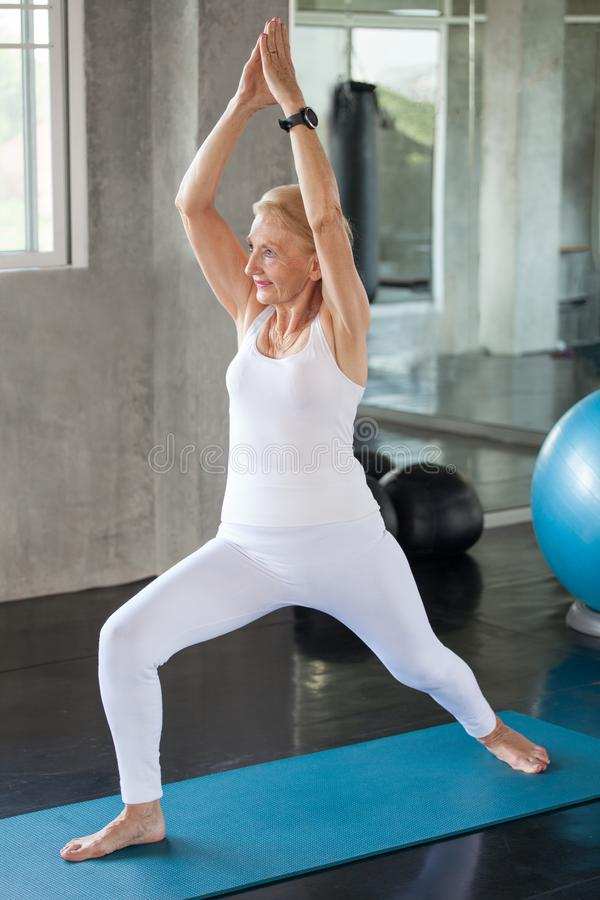 Senior woman Doing yoga in fitness gym. aged lady exercising.  Old female workout .Mature sport training.rehabilitation.elderly royalty free stock photography