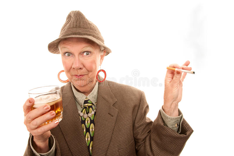 Senior woman in drag with cigarette and alcohol. Senior woman in tweed smoking and holding alcohol stock photos