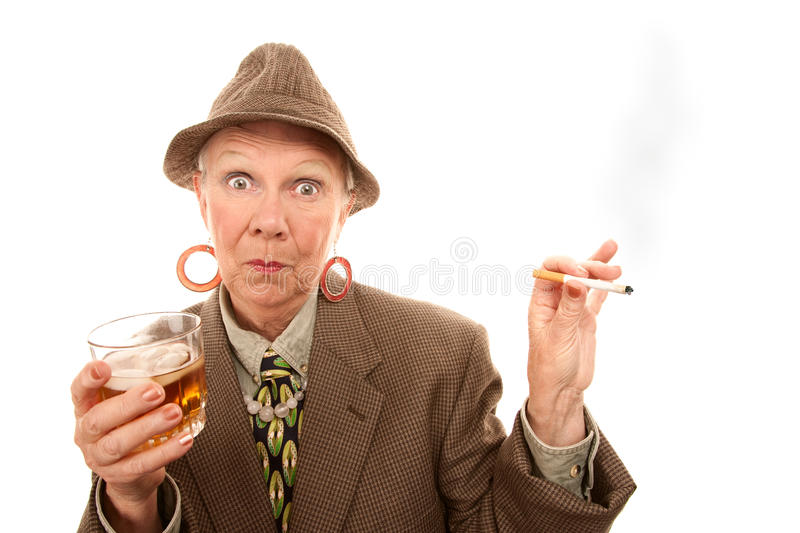 Senior woman in drag with cigarette and alcohol. Senior woman in tweed smoking and holding alcohol stock image