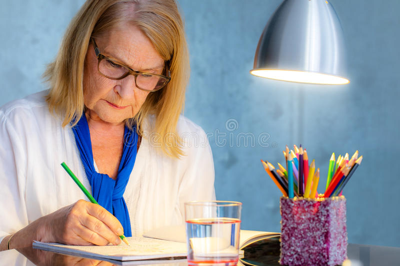 Senior woman drawing in color book for adults. stock photo