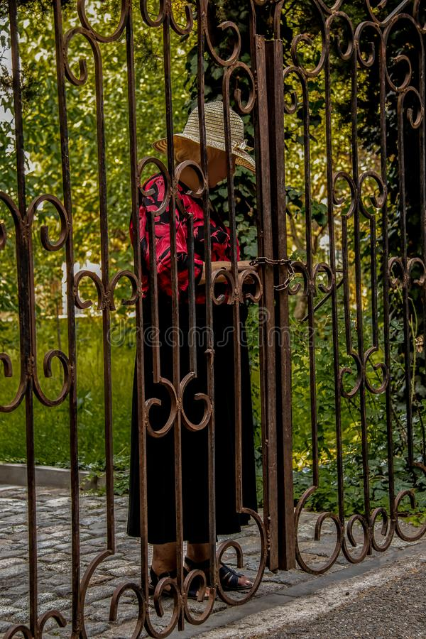 Senior woman in dress and hat locks wrought iron gate at property entrance with chain and padlock - lush vegetation and royalty free stock photography