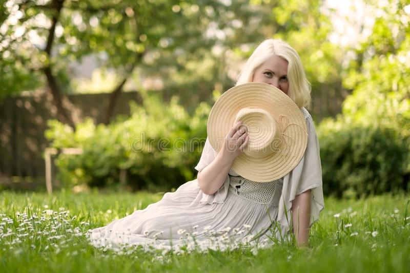 Senior woman in dress sitting on grass at the park royalty free stock photos