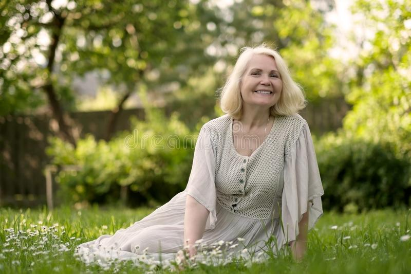 Senior woman in dress sitting on grass at the park stock photo