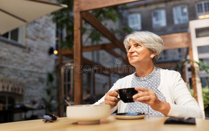Senior woman drinking coffee at street cafe stock photography