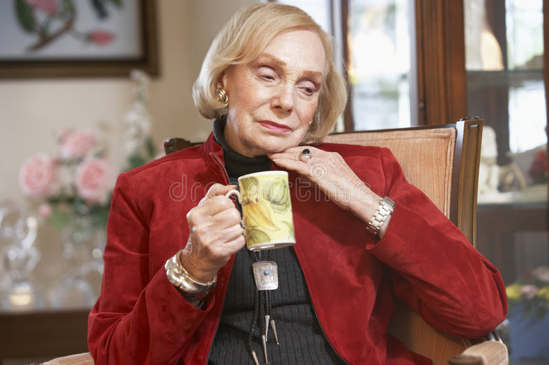 Senior woman drinking hot beverage royalty free stock images