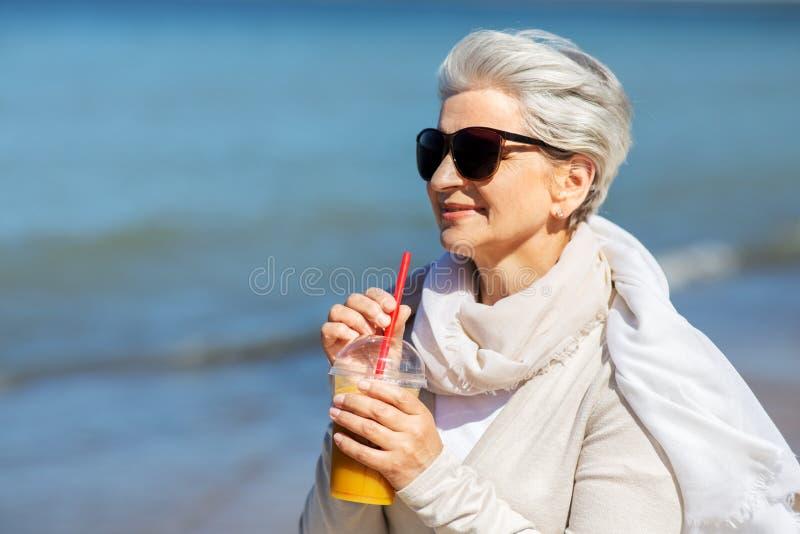 Senior woman drinking orange juice on beach. People and leisure concept - senior woman in sunglasses drinking shake, orange juice or smoothie on beach in estonia royalty free stock image