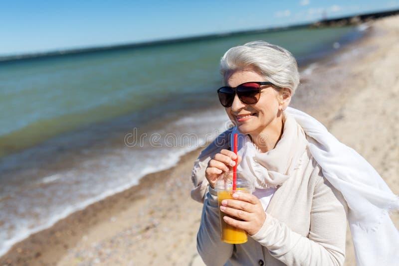 Senior woman drinking orange juice on beach. People and leisure concept - senior woman in sunglasses drinking shake, orange juice or smoothie on beach in estonia stock image