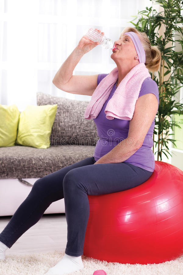 Senior woman drinking water after training at home royalty free stock photo