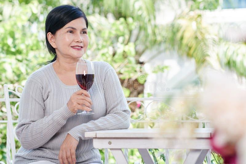 Senior woman drinking wine royalty free stock photo