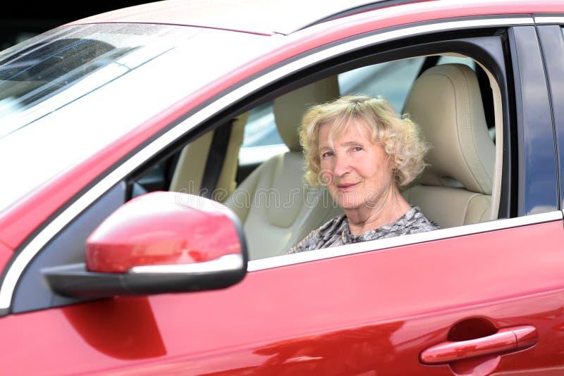 Senior woman driving the car. Happy healthy senior woman driving modern red car - active retirement concept stock photos