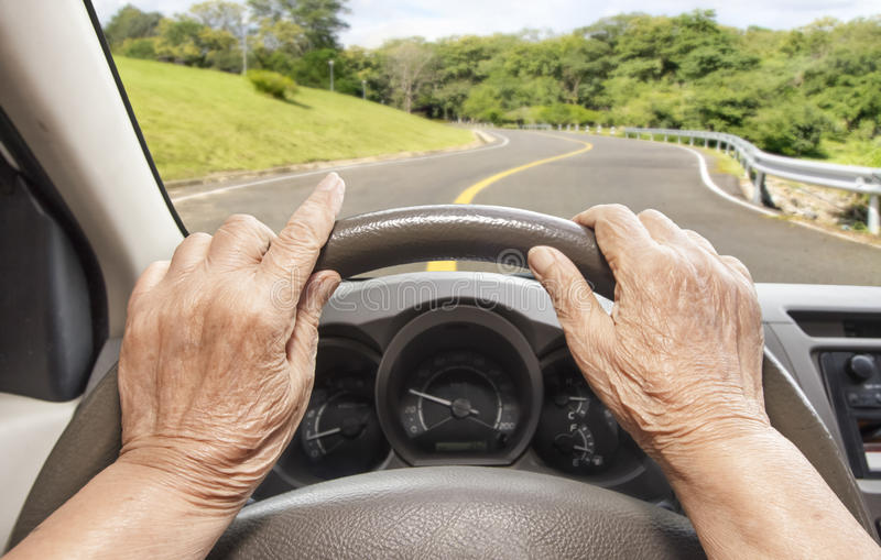 Senior woman driving a car on highway royalty free stock photography
