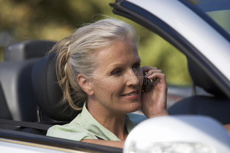 A senior woman driving a car whilst on a cell phone royalty free stock photos