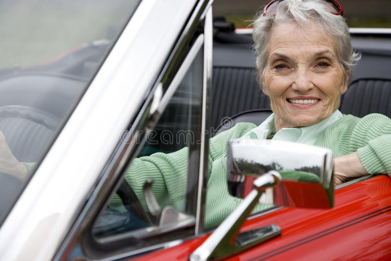 A senior woman driving a sports car royalty free stock images