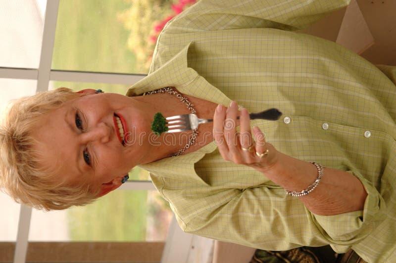 Senior woman eating broccoli. A healthy senior woman holding broccoli on a fork stock image