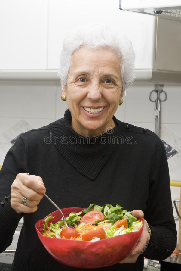 Senior woman eating a healthy salad. At the kitchen royalty free stock photography
