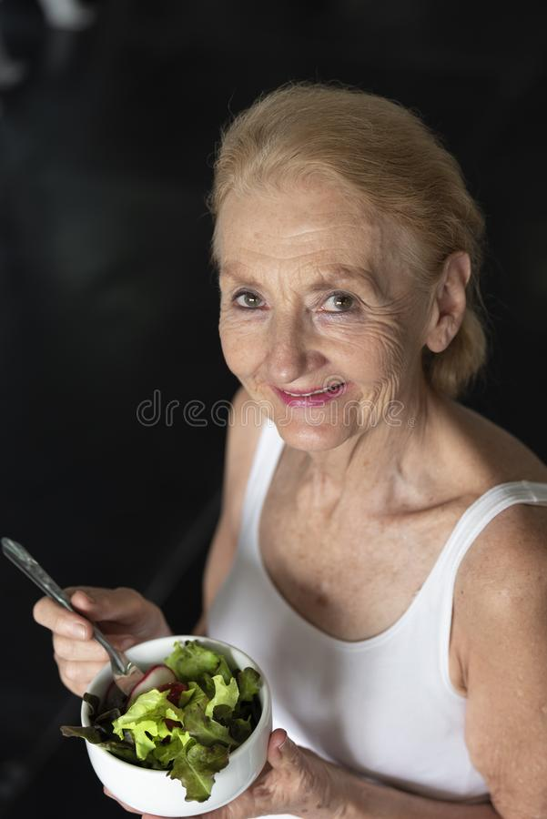 Senior woman eating healthy salad. elderly health lifestyle concept stock photography