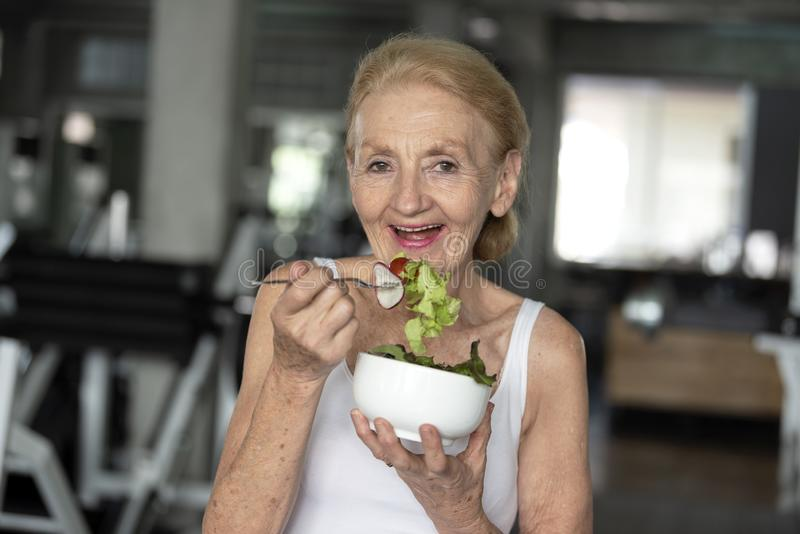 Senior woman eating healthy salad. elderly health lifestyle concept.  stock photo