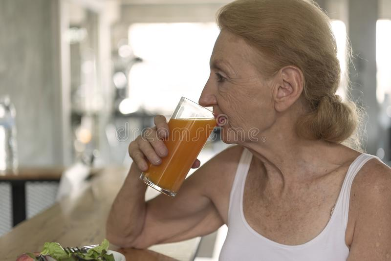 Senior woman eating healthy salad and orange juice. elderly health lifestyle concept.  stock image