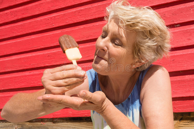 Senior woman eating ice cream while standing by hut stock photos