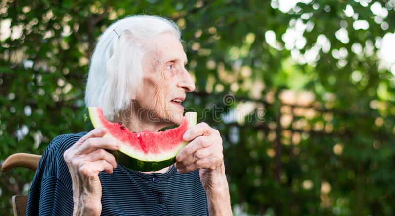 Senior woman eating watermelon outdoors stock photo