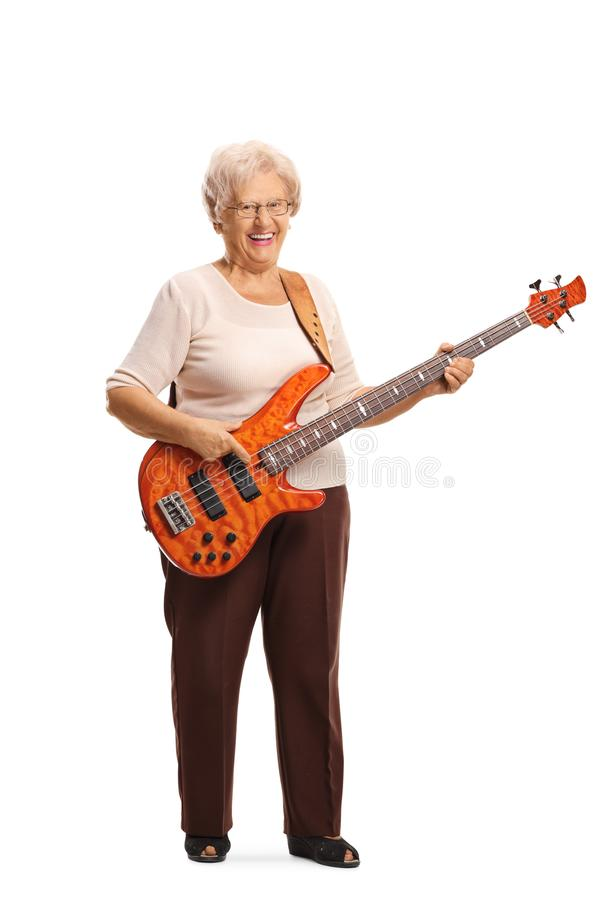 Senior woman with an electric bass guitar smiling at the camera. Full length portrait of a senior woman with an electric bass guitar smiling at the camera stock photos