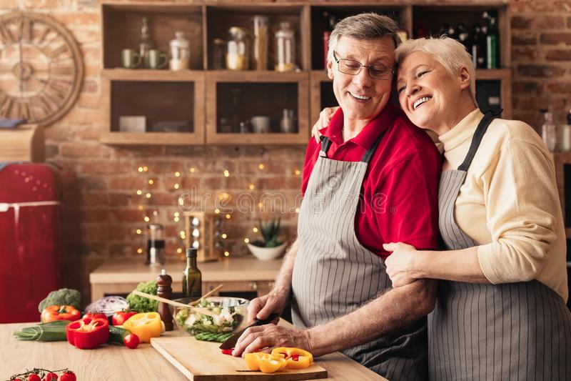 Senior woman embracing her cooking man at kitchen stock photo