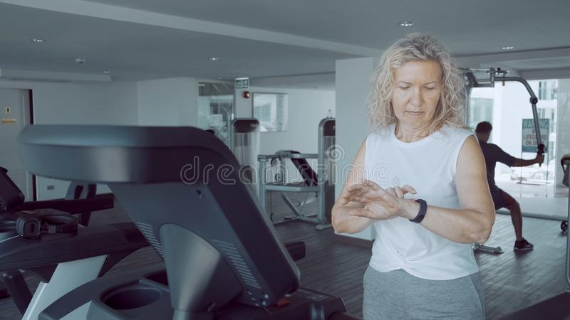 Senior woman is engaged on a treadmill in the gym with a sports cardio clock stock photo