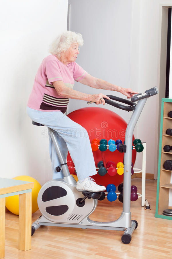 Senior Woman Exercising On Bike stock image
