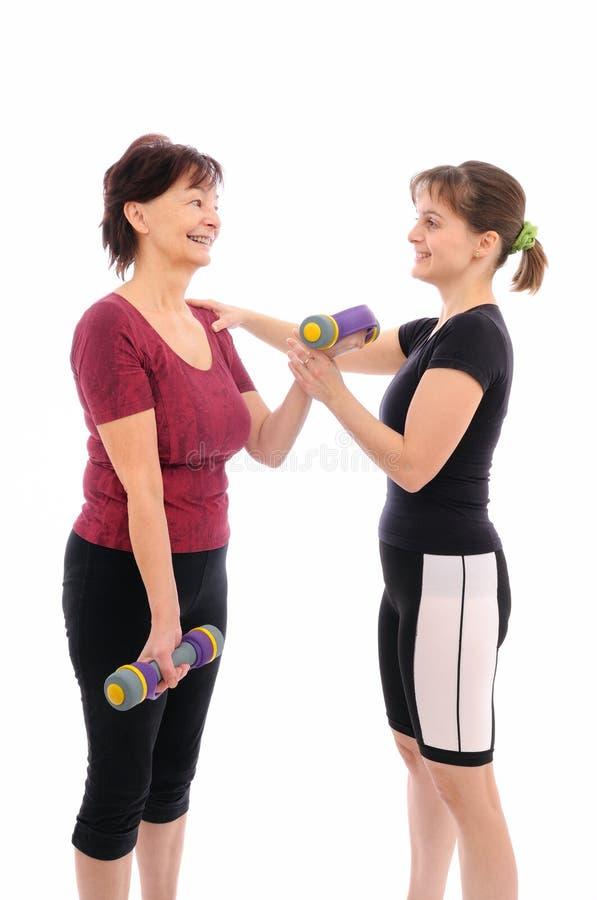 Senior woman exercising with coach stock photo