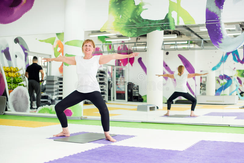 Senior woman exercising in fitness center royalty free stock photography