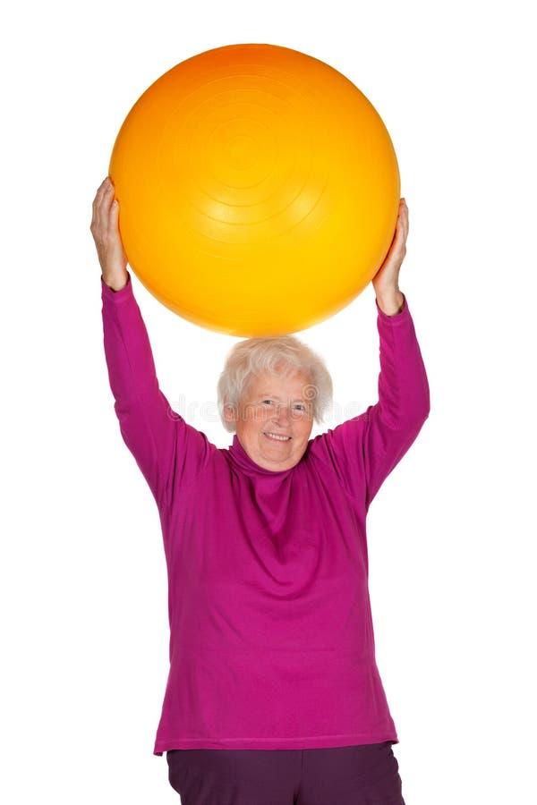 Senior woman exercising with gym ball stock photography