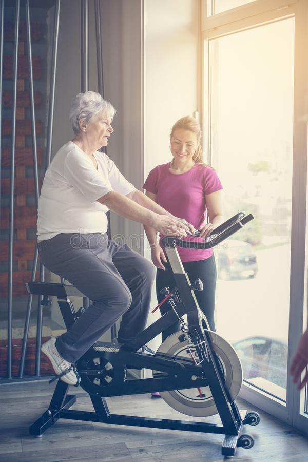 Senior woman exercising on stationary bikes in fitness class. stock photography