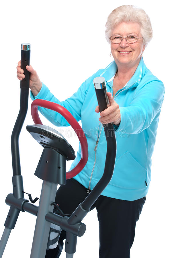 Senior woman exercising on stepper. Attractive senior woman at health club, exercising on stepper stock photography