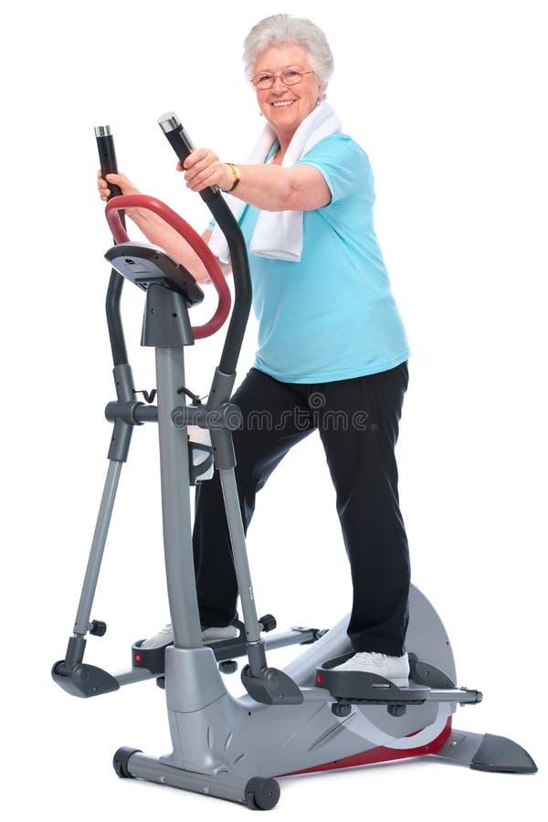 Senior woman exercising on stepper. Attractive senior woman at health club, exercising on stepper royalty free stock photos
