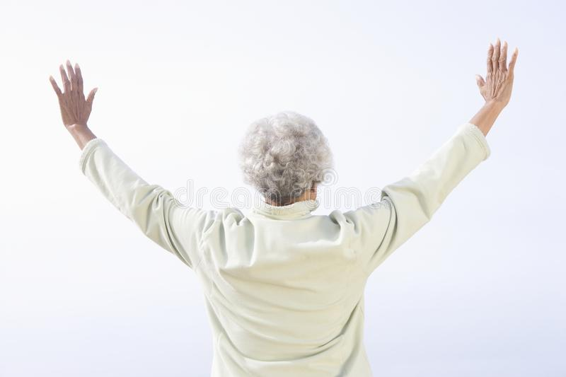 Senior Woman Facing Sea With Arms Raised Stock Image