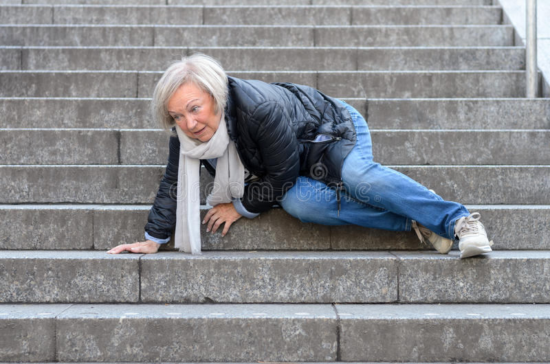 Senior woman falling down stone steps outdoors royalty free stock photo