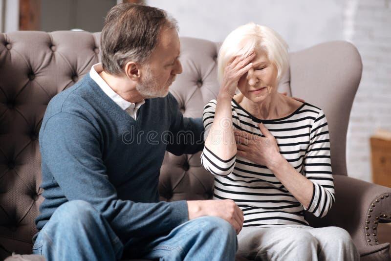 Senior woman feeling bad near her husband stock images