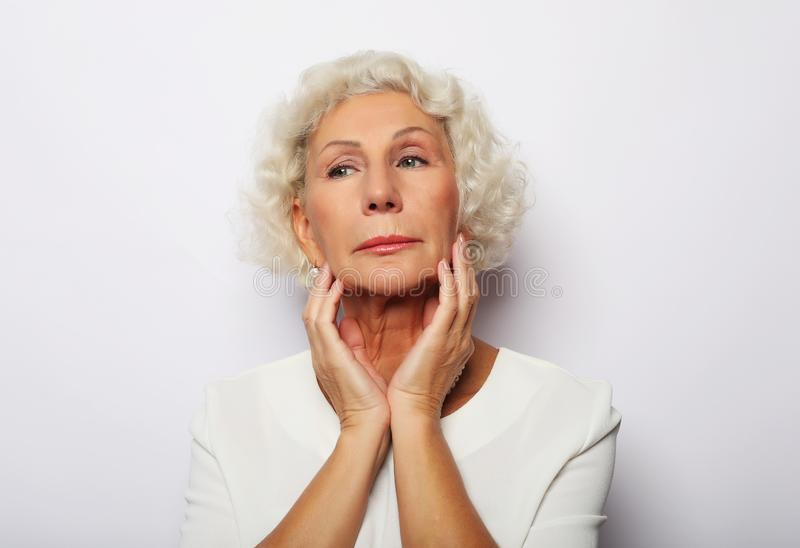 Senior woman feeling blue worried about problems, pensive upset sad middle aged grey haired lady royalty free stock image
