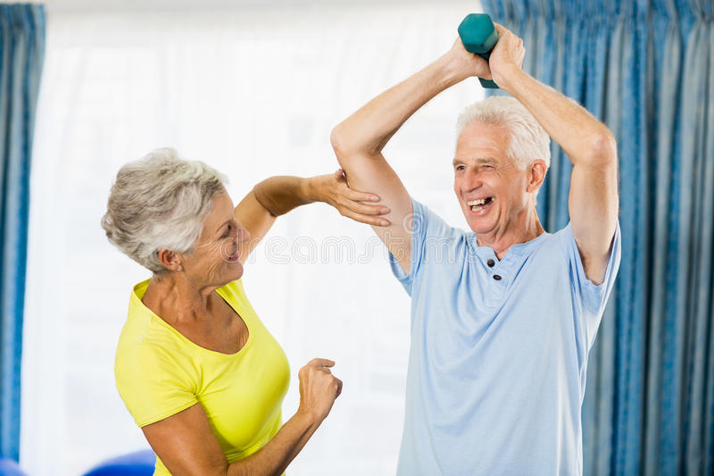 Senior woman feeling muscles of man stock photo