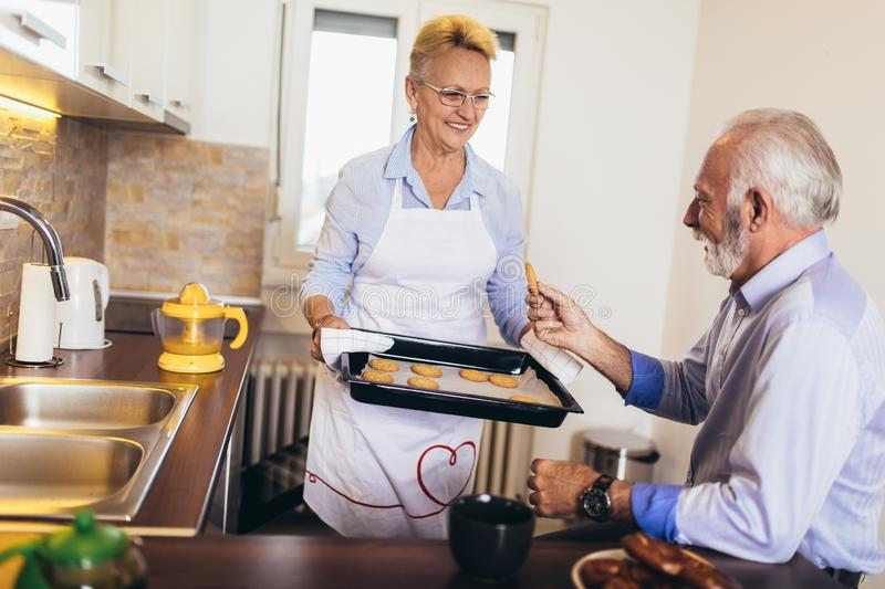 Senior woman with fresh baked cookies with his husband royalty free stock photography