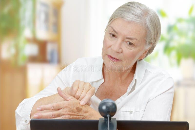 Senior woman computer webcam mole stock photo