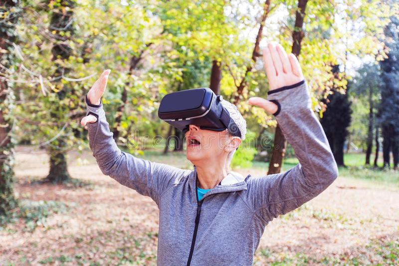 Senior Woman Fun With Virtual Reality Headset In Forest stock photos