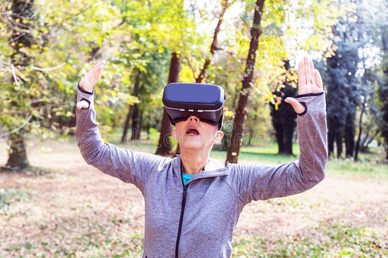Senior Woman Fun With Virtual Reality Headset In Forest stock image