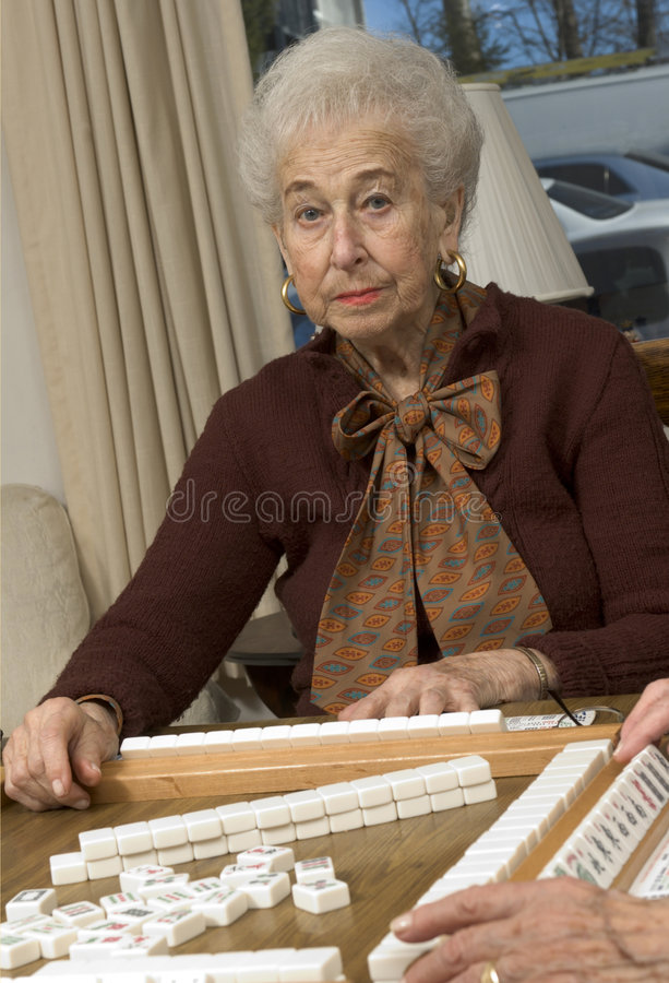 Senior woman at the game table royalty free stock photography