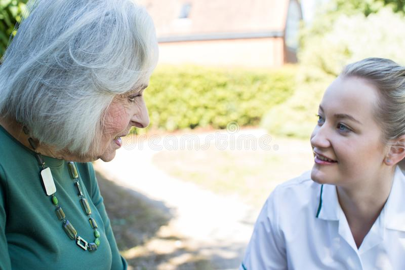 Senior Woman In Garden Talking With Female Carer royalty free stock photography