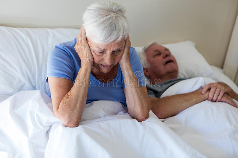Senior woman getting disturbed with man snoring on bed stock photo