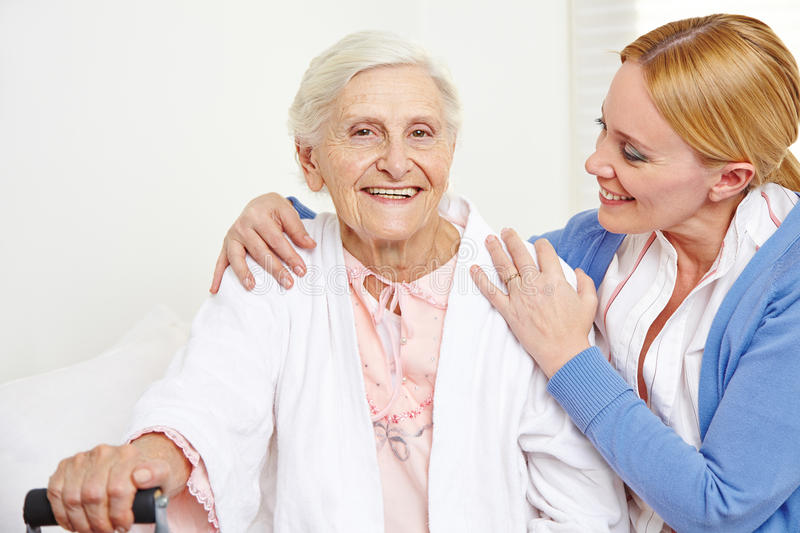 Senior woman getting geriatric care. Happy senior women getting geriatric care at home from her daughter royalty free stock image