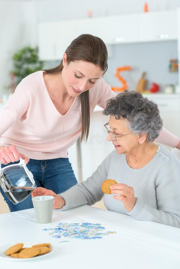 Senior woman getting helped with breakfast royalty free stock images