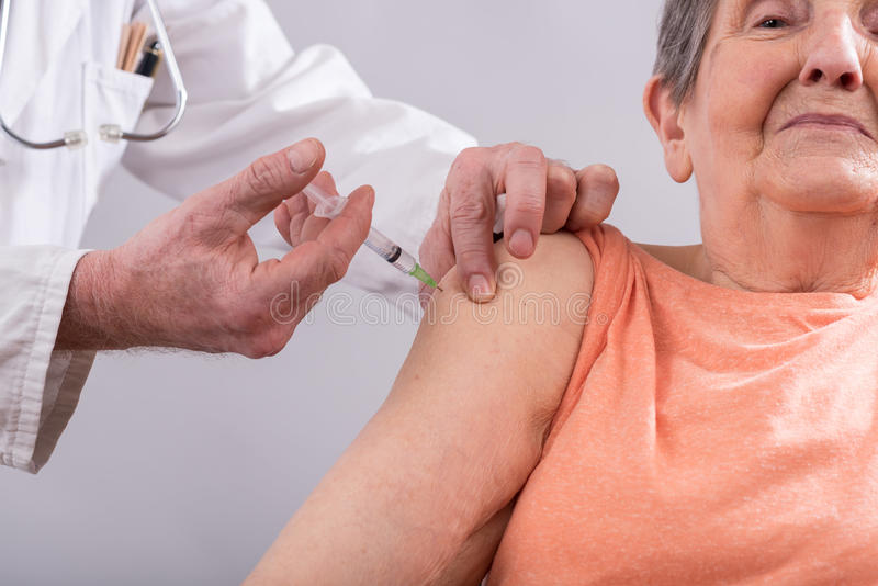 Senior woman getting an injection royalty free stock photos