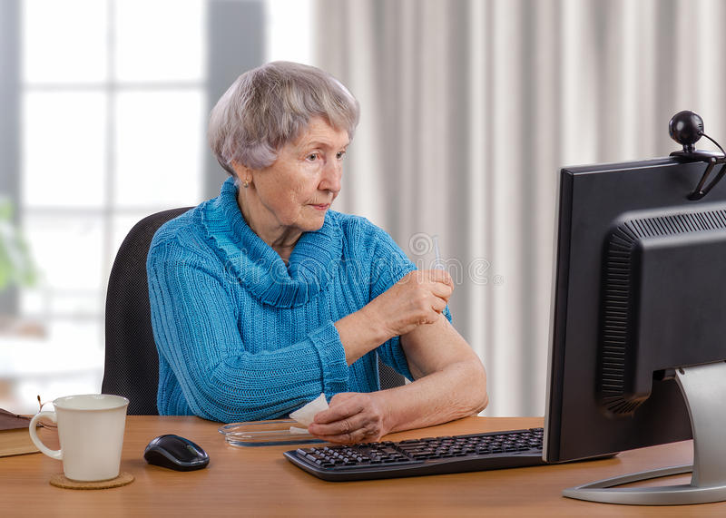 Senior woman gives an injection with telemedicine guidance. Old woman tries to give an intramuscular injection for herself. Grey-haired woman sits at wooden desk stock image